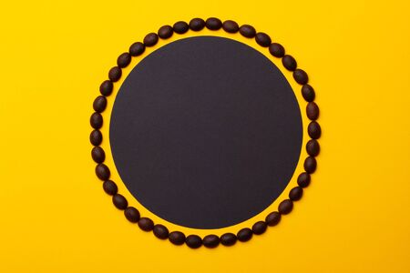 Creative composition of coffee beans in the form of a circle with black sticker on a yellow paper background.