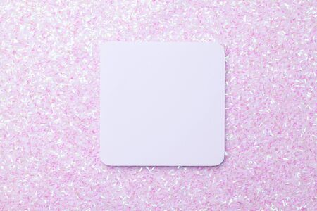 White sticker on the background of a brilliant rainbow background from a variety of small sequins.