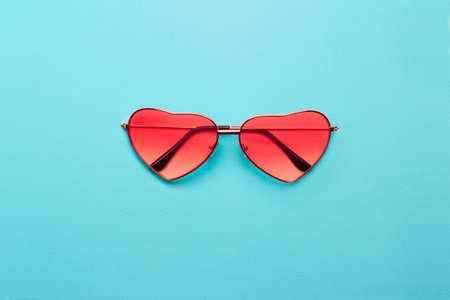 Bright orange heart-shaped glasses on  turquoise