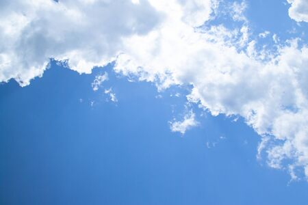 White fluffy clouds in a bright blue sky on a sunny day.