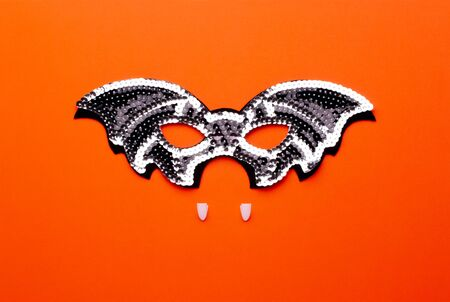 Conceptual halloween flat lay on a bright orange background. Black bat-mask with shiny sequins and vampire fangs as a symbol of halloween parties.