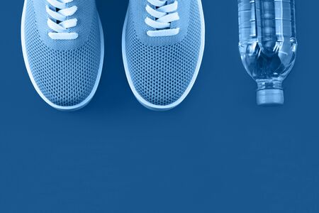 Photography on the theme of the trend color 2020. Bright blue sneakers on paper background with a place for an inscription.