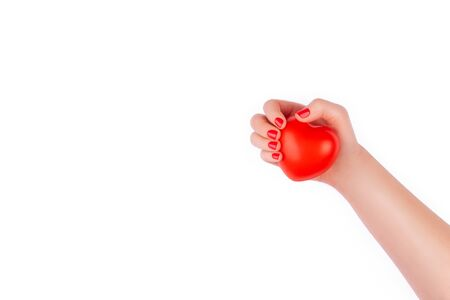 Female hand holds a toy heart showing perfect bright manicure in red on a white background.