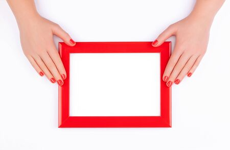 Beautiful healthy female hands with perfect bright red color manicure hold a frame for inscription on a white background. Reklamní fotografie
