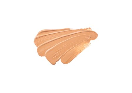 Bright beige smear of foundation in the form of a group of diagonal strokes isolated on a white background.