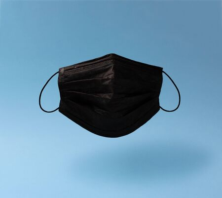 Creative composition on the theme of protective equipment from Covid-19. Levitating real black surgical mask with soft shadow on a blue background.