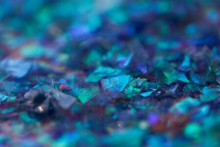 Abstract blurred blue toned background with beautiful bokeh effect. Macro photo of small rainbow glossy pieces of decorative foil in blue shades.