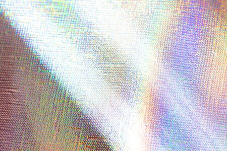 Photo of a real light rainbow crumpled holographic background with a skin texture with rays daylight.