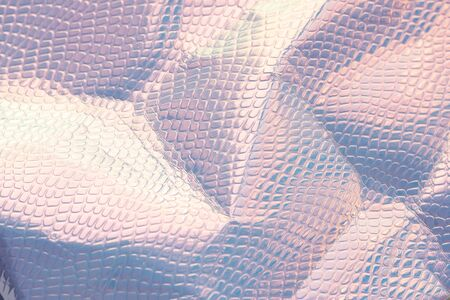 Blurred light rainbow crumpled holographic background with a reptile skin texture in blue toned. Reklamní fotografie