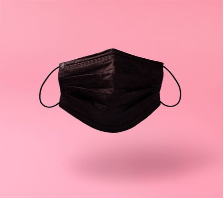 Creative composition on the theme of protective equipment from Covid-19. Levitating real black surgical mask with soft shadow on a pink background. Reklamní fotografie
