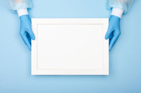 Actual photo on the theme of the disease against coronavirus. Hands in medical gloves hold a poster with a place for inscription on a blue background.