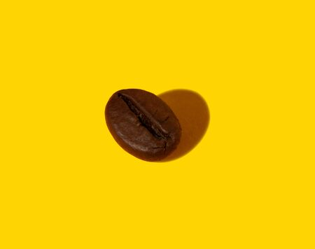 Creative composition of a real closeup macro photography of a coffee bean with a hard shadow in the shape of a heart.