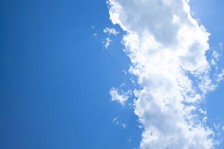 White fluffy clouds in a bright blue sky on a sunny day. Reklamní fotografie