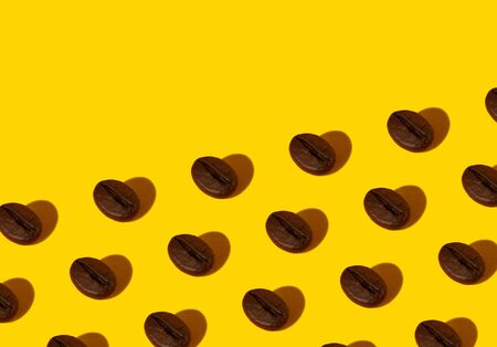 Creative bright collage of real macro photos of selected coffee beans on a yellow background with a hard shadow in the shape of a heart with a place for inscription. Reklamní fotografie