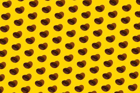 Creative bright collage of real macro photos of selected coffee beans on a yellow background with a hard shadow in the shape of a heart with a place for inscription. 免版税图像