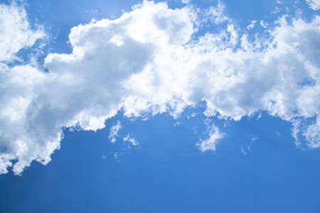 White fluffy clouds in a bright blue sky on a sunny day. 免版税图像