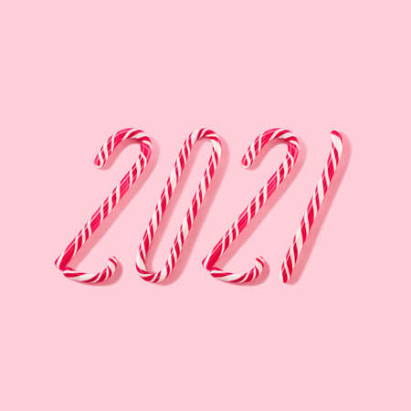 Pale pink conceptual composition on a New Year's theme. A collage of Christmas candy canes in the form of the inscription 2021 on a pink background. 免版税图像