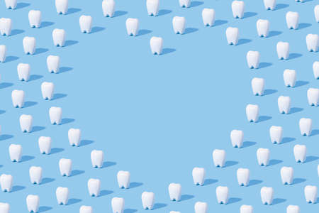 White teeth pattern on a blue paper background with text place.