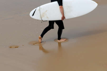 plucky: A surfer is walking on the beach  Stock Photo