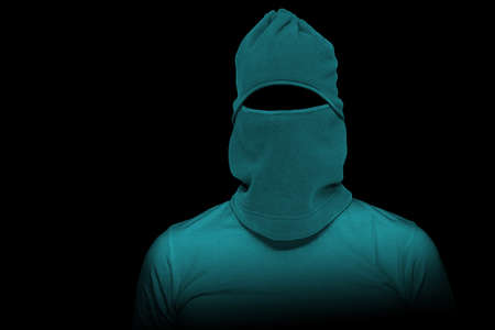 Thief with green mask on his face on black background.