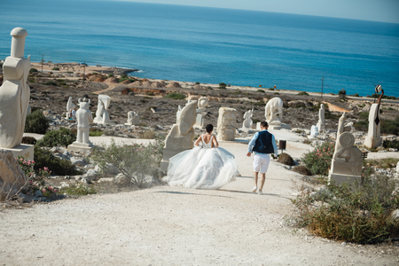 Beautiful smiling young bride and groom walking on the beach, kissing and having fun, wedding ceremony near the rocks and sea. Wedding ceremony on coast of Cyprus