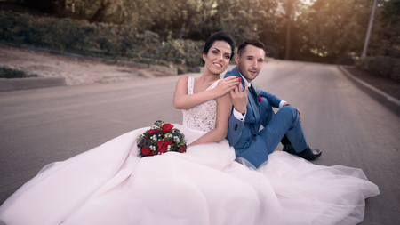 Wedding couple on the nature is hugging each other. Beautiful model girl in white dress. Man in suit. Beauty bride with groom. Female and male portrait. Woman with lace veil. Lady and guy outdoors Zdjęcie Seryjne