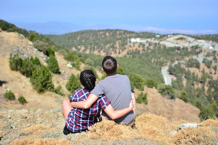 Active couple rests on a mountain peak looking on a mountain landscape