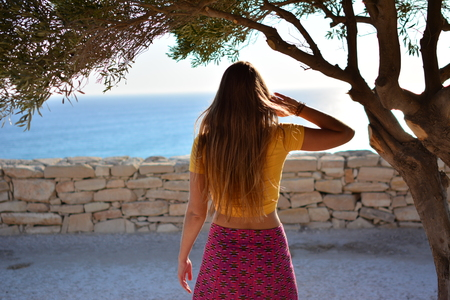 Girl sits on a cliff under an old tree with a beautiful view of the sea and mountains. Vacation in the European resort. Travel and leisure.
