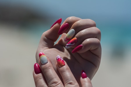 On the sand are well-groomed young hands with a beautiful bright manicure on the nails Zdjęcie Seryjne