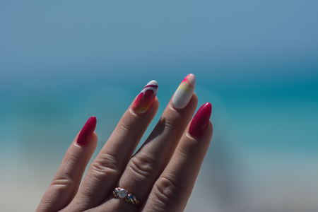 On the sand are well-groomed young hands with a beautiful bright manicure on the nails Zdjęcie Seryjne - 122112864