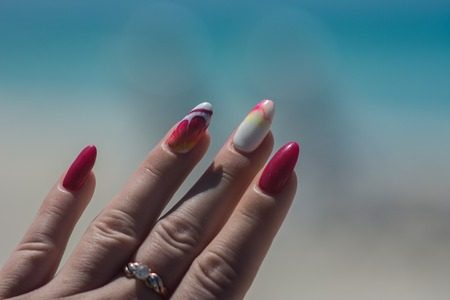 On the sand are well-groomed young hands with a beautiful bright manicure on the nails Zdjęcie Seryjne - 122112866