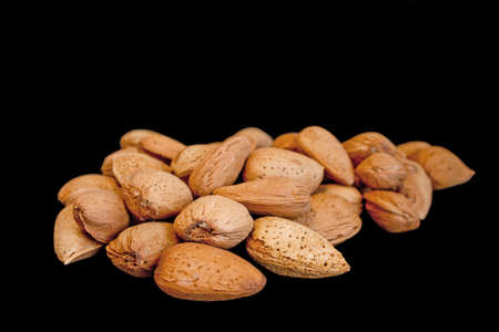 nutshell: Almonds in nutshell  in isolated over black