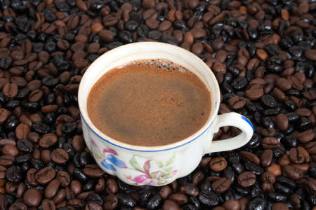 coffeebeans: The cup of coffee on coffee-beans background Stock Photo