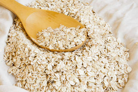 Dry rolled oats in wooden spoon photo