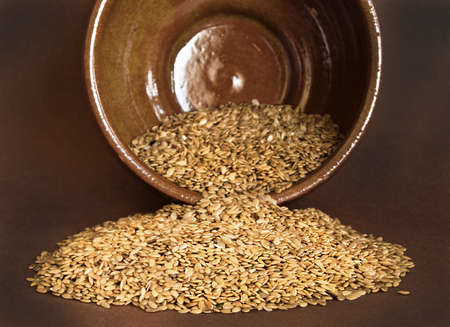 Flax seed on ceramic bowl on broun background Stock Photo - 16824685