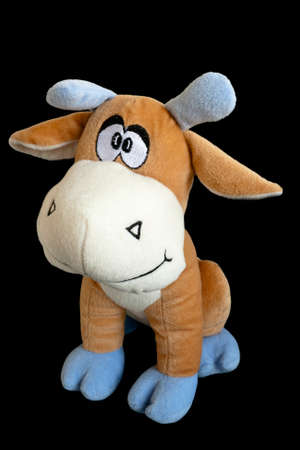 babyhood: Soft toy a plush calf isolated on black background