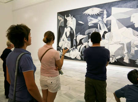 """Madrid-July 5: Unknown people standig before the most famous painting by Pablo Picasso """"Guernica"""" in Museo Nacional Centro de Arte Reina Sofia - Madrid on July 5, 2009"""