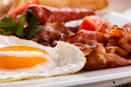 English breakfast with bacon, sausage, fried egg, baked beans and tea or orange juice Фото со стока - 37827855