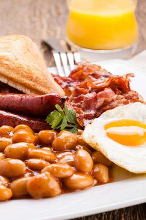 베이컨, 소시지, 튀긴 계란, 구운 콩 및 차 또는 오렌지 주스가있는 영국식 아침 식사 스톡 콘텐츠