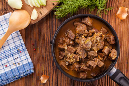 Preparing beef stew - wooden background Stock Photo