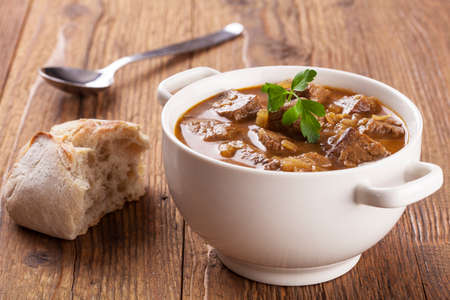 Beef stew served with bread in a plate on a wooden background