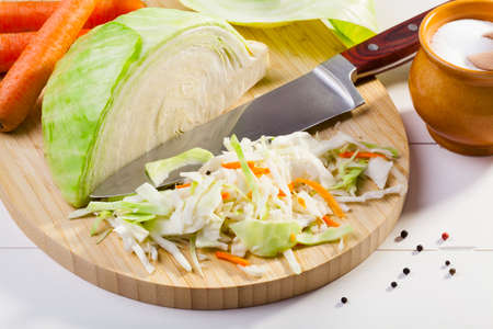 Fresh cabbage prepared for pickling on woodboard photo