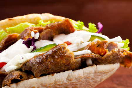 Beef Kebab in a bun with garlic sauce on woodboard Stock Photo