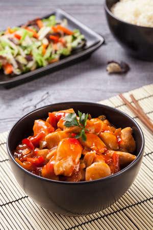 중국 치킨 달 콤 하 고 신 소스, 쌀과 야채 woodboard에 제공