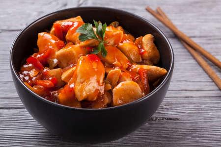中国語甘いチキン甘酸っぱいソース、ご飯と野菜の woodboard 添え