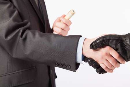Business concept - a man in a suit takes a bribe from the offender
