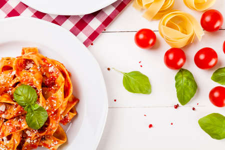 pasta: Pasta tagiatelle with tomato on white woodboard Stock Photo