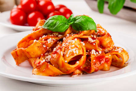 pasta sauce: Pasta tagiatelle with tomato on white woodboard Stock Photo