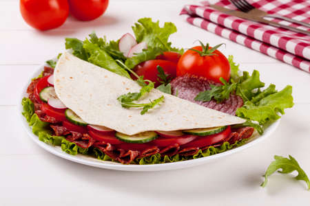 Italian Piadina Romagnola with salami and vegetables on white woodboard photo