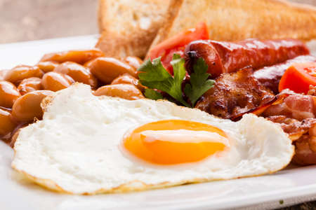 english food: English breakfast with bacon, sausage, fried egg, baked beans and tea or orange juice